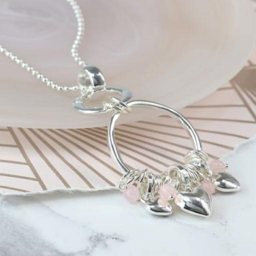 Peace Of Mind. Long silver plated necklace with a double hoop pendant featuring a cluster of silver plated rings, pink c